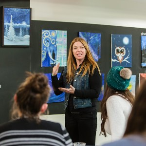 A woman with long red hair stands in front of a group of students teaching a workshop. Behind her many different paintings hang on the wall.