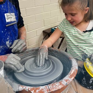 A young blonde girl molds grey clay with her hand on a pottery wheel.