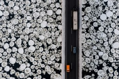 "Poland, Kiezmark, A lorry and cars travel on a road past the ice covered Vistula River near the village of Kiezmark during Winter. 54°15'24.24""N 18°56'47.80"" Kacper Kowalski: OVER / Side Effects at Galerie XII, Los Angeles. Photo courtesy of the gallery."