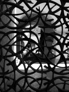 Black and white photo of an ornate iron gate and a person seen through the other side