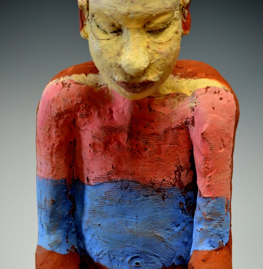 close view of figure, with painting reflected onto it. About isolation during Covid19.