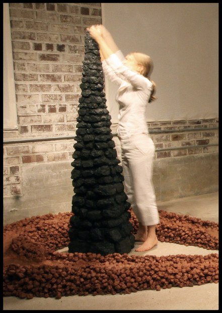 2013, Recycled red clay, volcanic rock, performer in white, black adobe, and coal