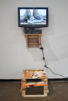 "TV, wood, steel, porcelain, ratchet strap, video (loop), US Army desert combat boot, extension cable, RCA cables, 100mph tape, 80x32x28"", 2016"