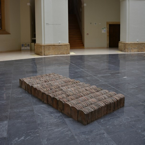 All the tiles were collected from a roof of an old house, which was condemned to demolition. Its smashed and shattered roof becomes rearranged and pieced back together to a symbolic bed – a site of rest, birth or death. Bed that incorporates the most intimate moments of life and presents a sort of tiny dwelling in the midst of a house.
