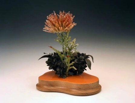 "black clay, resin, plastic flowers, aged walnut, 10 1/2"" x 9"" x 12 1/2"""