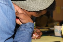 Ntokozo Wandile Mbokazi writes the poem he will later perform. IMAGE: Chelsea Haith