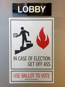 """In Case of Fire, Use Stairs"" warning label with substituted text reading ""In Case of Election, Get Off Ass"" accompanied by a figure running down stairs carrying a ballot icon"