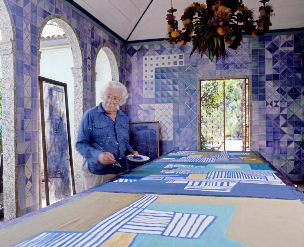 Roberto Burle Marx painting a tablecloth in the loggia of his home, 1980s; the azulejo tile walls and chandelier composed of fruit and flowers on a metal armature are his work. Photograph © Tyba.