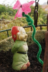 Gnome catching a droplet under a flower in Spring