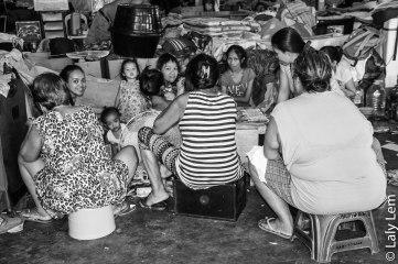 Dans un ancien gymnase aménagé en habitations (des couvertures font office de mur en guise de séparation), des mères entourées de leurs enfants improvisent une partie de belote.