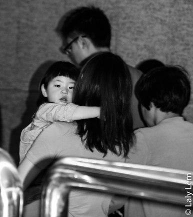 Dans le métro de Pekin, une petite fille agrippée à sa maman.