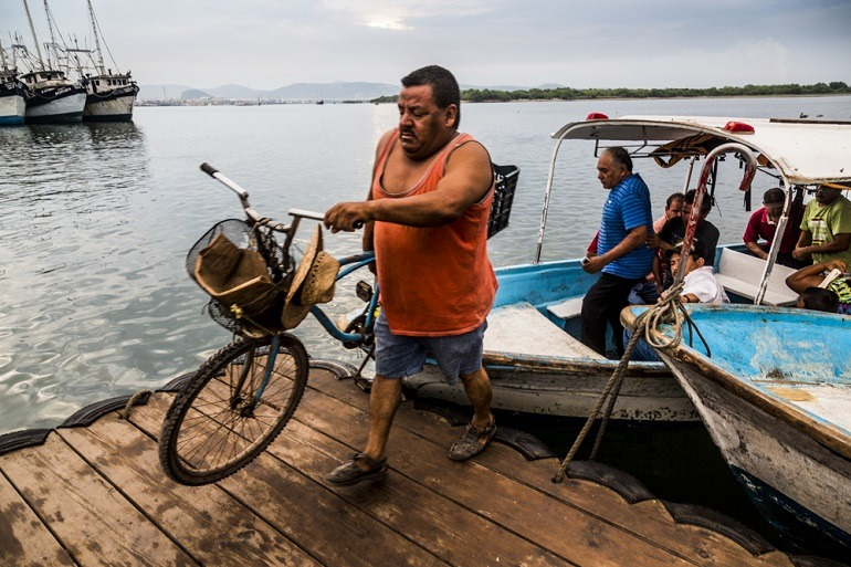 Image: Man with Bicycle. A man carries his bicycle off the boat as he makes his way to the fish market is one images taken by photographer Matt Mawson