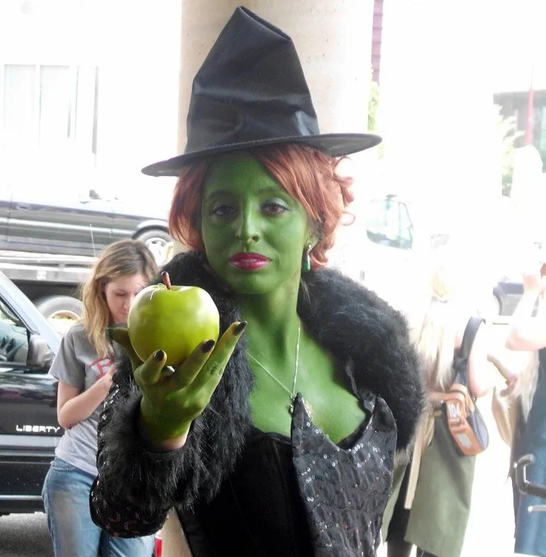 Image of Witch, a disney character hands out an apple to audience at Otakon -Baltimore Convention Center.
