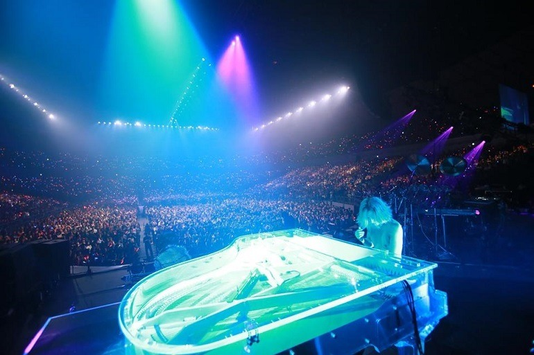 Image: Yoshiki performs on the piano under the stage light at the Madison Square Garden to  ecstatic fans