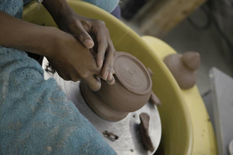 Image: Potter at the potter's wheel at Baltimore Clayworks, one of Baltimore's to contemporary art galleries
