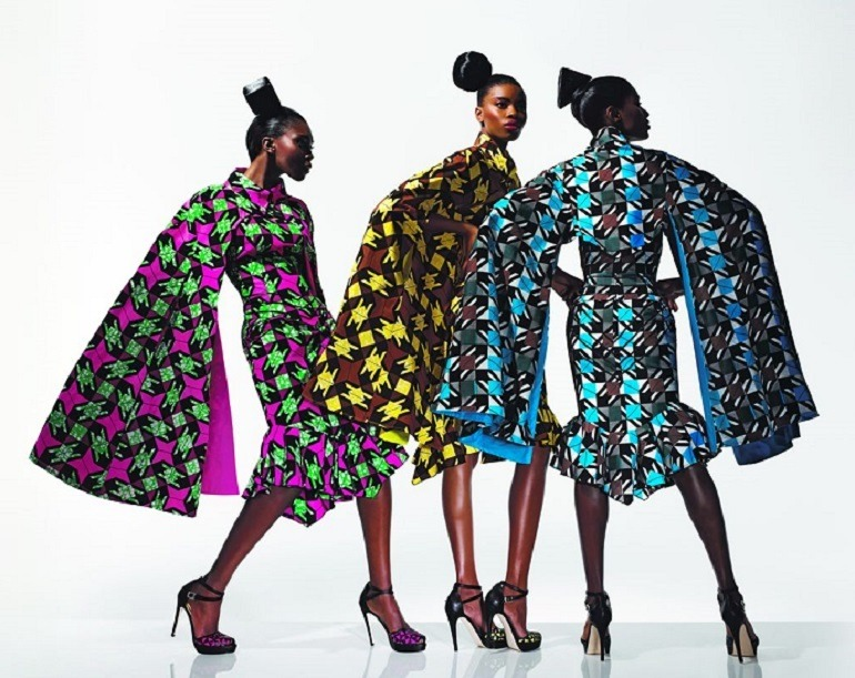 Image: Three beautiful women show off their dresses made from wax printed fabrics with bold patterns that have be described as authentic African