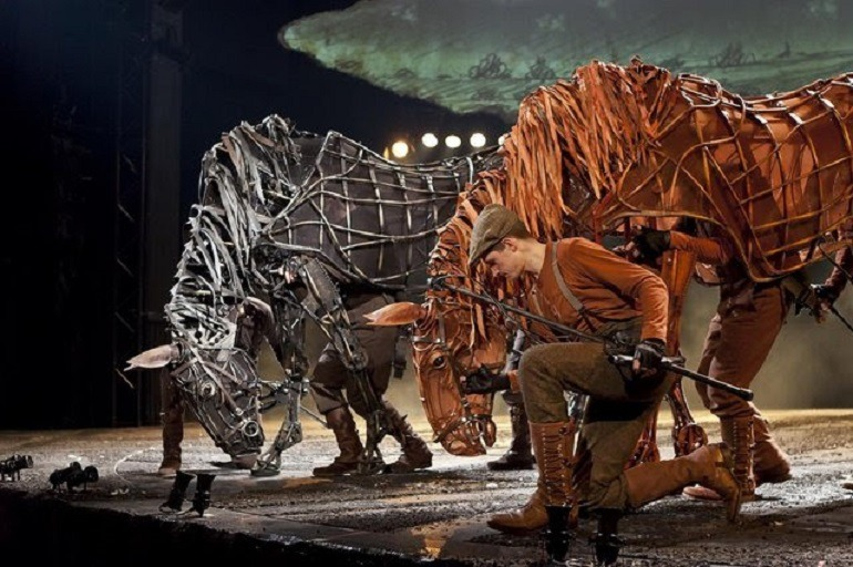 Image: War Horse puppet masters on stage in a depiction of World War I through the eyes of Joey the horse and farm boy Albert