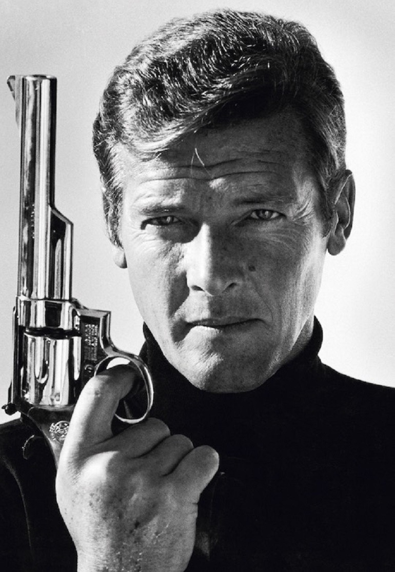 Image: portrait photograph of British actor Roger Moore poses with a gun as James Bond taken in the late 1970s by Terry O'Neill is one of the portrait photographs in Legend Passed