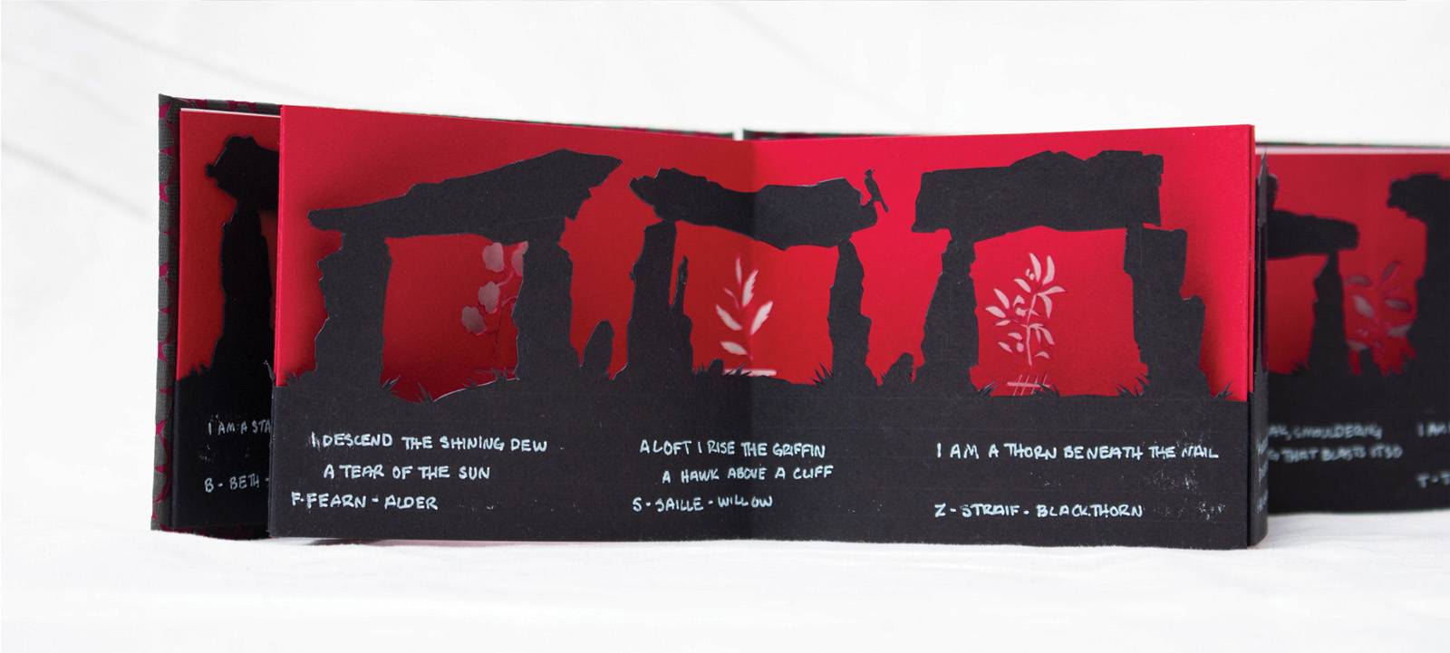 A spread from The Song of Amergin. The first layer has lines from the poem and paper-cut dolmens. The second layer has paper-cut plants.