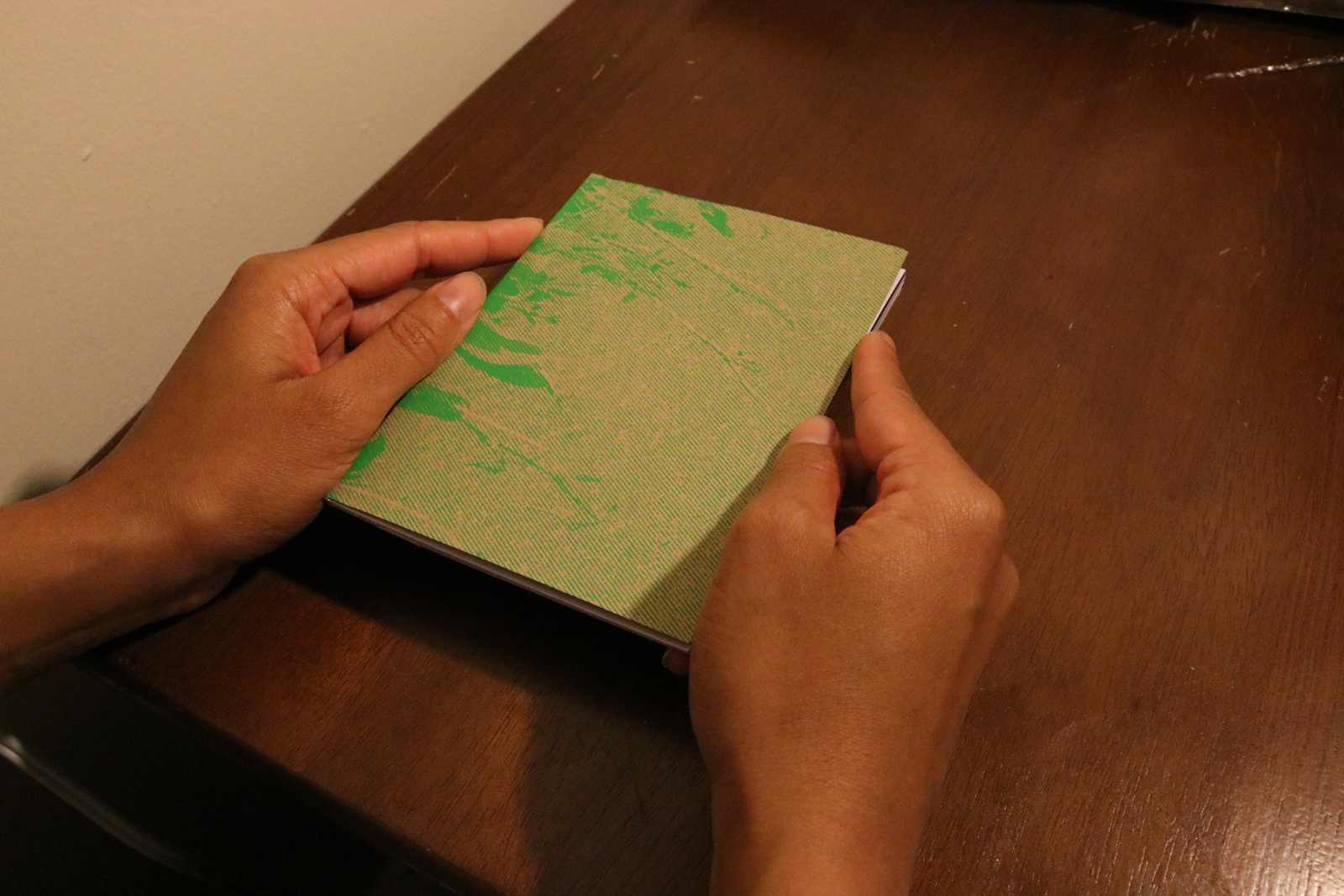 The front cover of Restoration. The image is of vines on asphalt in green ink screen printed on brown paper.