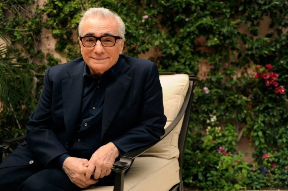 Martin Scorsese production design | Martin Scorsese Films | Director Martin Scorsese sitting in metal chair with white cushions in front of greenery in navy suit with glasses