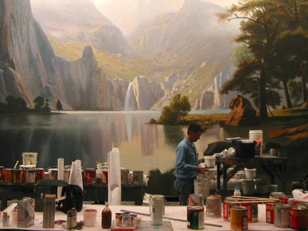 A scenic painter prepares his paint and tools in front of an epic landscape backdrop showcasing the Scenic Paint Department Roles