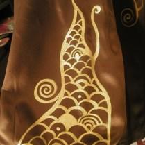 Golden pattern on satin fabric. Fragment