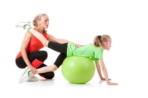 Full body shot of a little girl doing exercise with an instructor. Orange, green and black colors