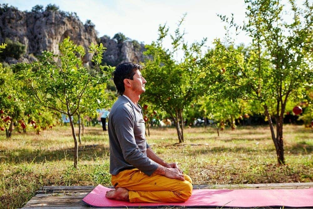 man meditating on the pad in pomegranate garden on mountain background