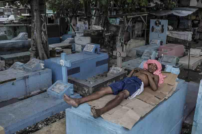 Homem dormindo sobre túmulo