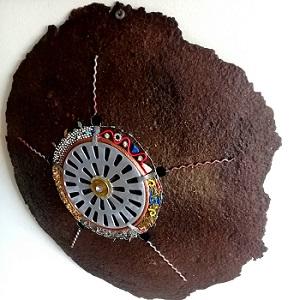 Claudia Seber. SOL URBANO ano 2019 dimensão 50 cm diâmetro (disco de arado oxidado;tampa de ralo;sucatas) R$ 400,00