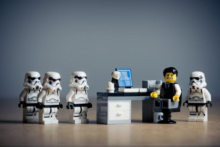 Bonecos Lego, um com roupa social, representando um chefe constrangido e funcionários representados por bonecos stormtrooper aparentando fazer uma reclamação.
