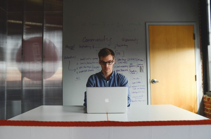Homem sentado em frente ao computador.