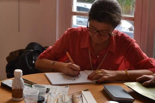 """Cécile Van Espen entrain d'écrire sur la première page de l'ouvrage """"Pau, autour de l'aquarelle"""". En premier plan, le matériel de peinture"""