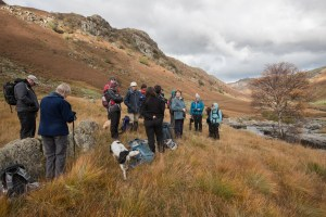 A group of people in a valley with fells.