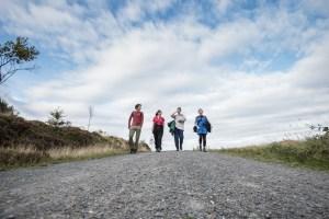 4 people walking along a path.