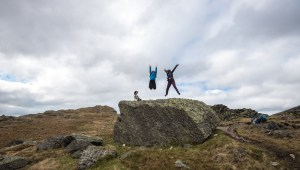 2 people jumping off a rock.