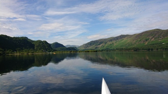 Derwentwater lake, still with cloud reflections and fells in distance.
