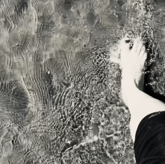 A foot stepping in to clear sea water with rippling sand below.
