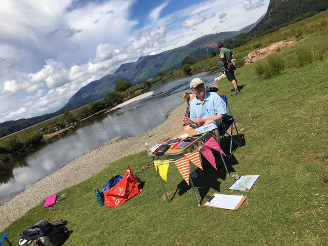Man sitting on table with butnung and postcards on the shores of derwentwater.