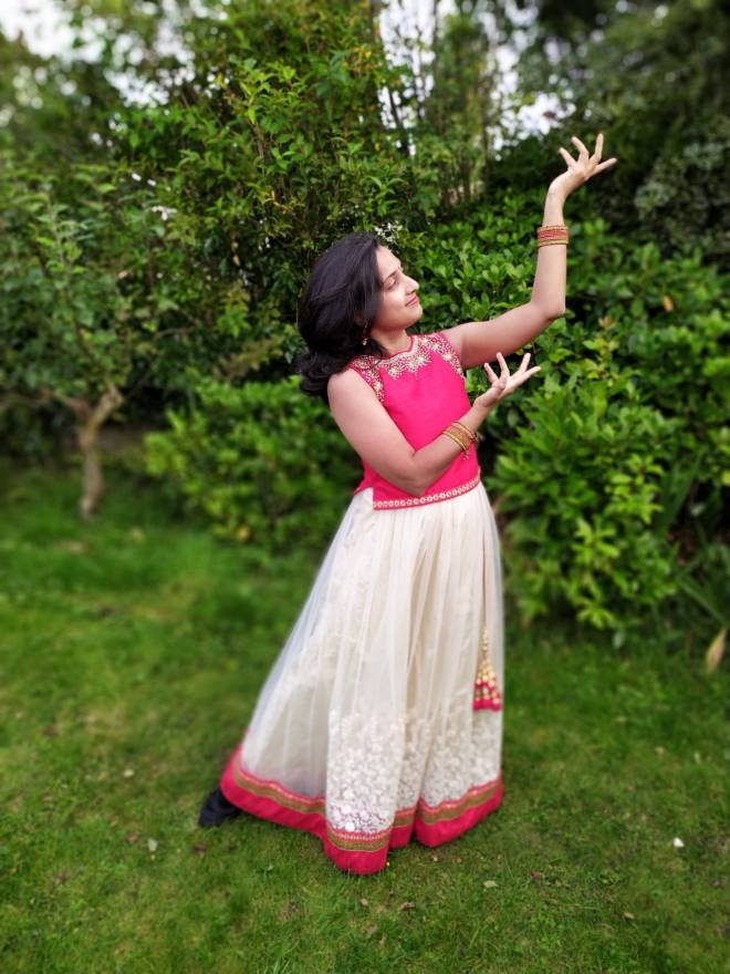 A woman in a park holds up her hands in a Bollywood dance pose.