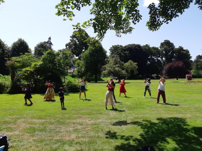 A group of people in a park doing a dance routine.