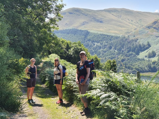 3 women stand on a rural path with ferns in verges and fells in distance.