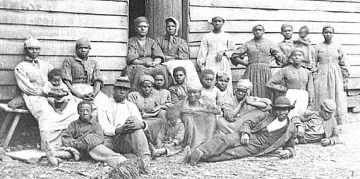 An image of enslaved people from a plantation, standing and sitting beside a wooden building.