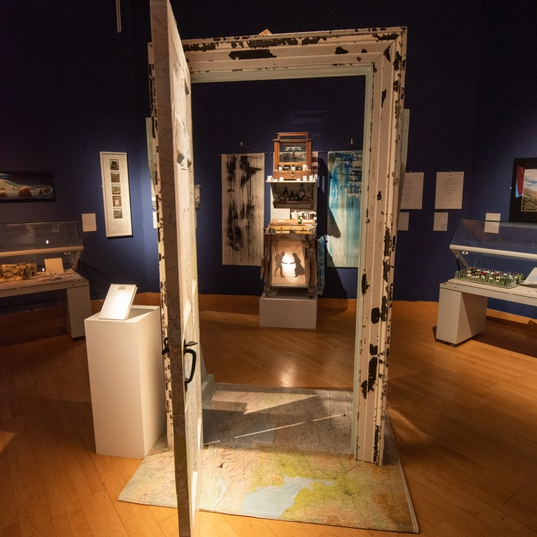 A doorway is installed in the centre of a gallery, and held open. Beyond it, a cabinet is visible, with a shadow-puppet scene lit up, and there are other paintings on the wall.