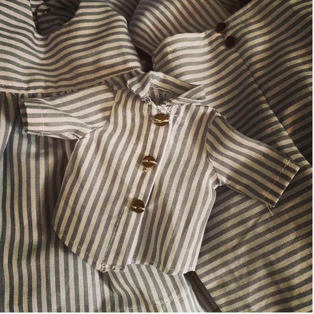 Small shirt made with striped material; a replica, in small size, of some of the shirts that would have been worn by enslaved people living on American plantation. The small shirt has three leather buttons, and is laid against other clothes made in the same material.