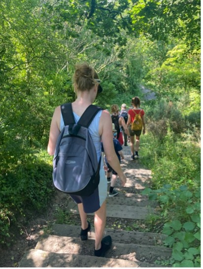 A photograph of people walking, showing a woman from behind. She is wearing a T Shirt and a bag on her back. It is obviously a hot day. The group is walking beneath trees, with sunshine on the leaves.