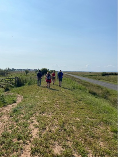 A photograph of four people walking on sun-dried grass, beside a road, with a cloudless sky.