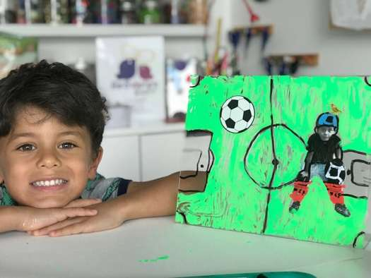 Boy posed next to finished mixed media artwork on plexiglass