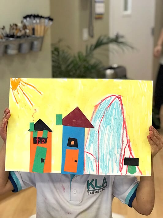 Boy holding up mixed media collage artwork of cities – Paul Klee Art for Kids